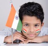 Gullig seende indisk unge med den indiska flaggan Royaltyfria Foton