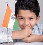Gullig seende indisk unge med den indiska flaggan Fotografering för Bildbyråer