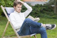 Gullig skäggig ung man som läser en bok i trädgården Arkivfoton