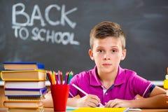 Gullig skolapojke som studerar i klassrum arkivbild