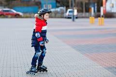 Gullig skolaungepojke som åker skridskor med rullar i staden Lyckligt sunt barn i skyddssäkerhetskläder som åker skridskor med royaltyfri foto