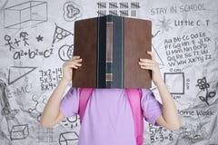 Gullig skolflicka som döljer hennes framsida bak en bok arkivbild