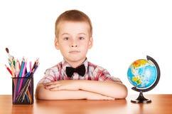 Gullig skolpojke, jordklot och blyertspennor på den isolerade tabellen Fotografering för Bildbyråer