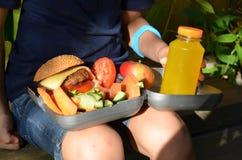 Gullig skolpojke som utomhus äter skolan från plasticklunchboxe Sund skolafrukost för barn Mat för lunch royaltyfria bilder