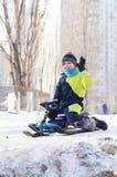 Gullig sledding för barn Litet barnpojke som rider en pulka i snön arkivfoto