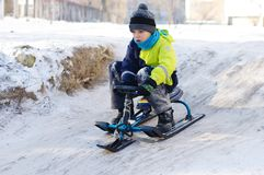 Gullig sledding för barn Litet barnpojke som rider en pulka i snön arkivbild