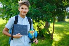 Gullig, smart ung pojke i blåa skjortaställningar på gräset med jordklotet och skolaryggsäcken, arbetsböcker Utbildning tillbaka  arkivfoto