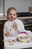 Gullig smutsig liten flicka som äter sund havregröt Arkivbild
