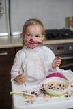 Gullig smutsig liten flicka som äter sund havregröt Arkivbilder