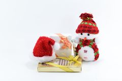 Gullig snögubbedocka på vit bakgrund med den röda hatten och gåvan, leksak för jul Arkivbild