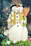 Gullig snögubbegarnering bredvid julträd bakgrund för ` s för nytt år för vinter royaltyfri foto
