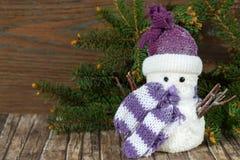 Gullig snöman i hatt och halsduk på en naturlig wood bakgrund Arkivbild