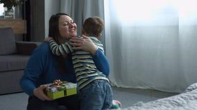 Gullig son som ger gåvaasken till mamman på dag för moder` s
