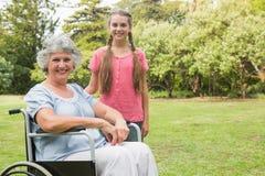 Gullig sondotter med farmodern i hennes rullstol Royaltyfri Bild