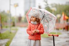 gullig sorgsenhet behandla som ett barn flickan i regnkörningarna till och med pölarna arkivbild