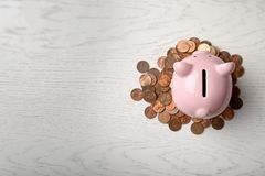 Gullig spargris och mynt på träbakgrund, bästa sikt fotografering för bildbyråer