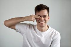 Gullig stående av den unga attraktiva le mannen i vit t-skjorta c arkivbilder