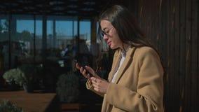 Gullig stads- flicka med smartphonen vid kafét stock video