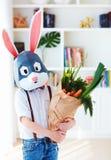 Gullig stilfull pojke, i polygonal easter kaninmaskering med en påse mycket av nya vårgräsplaner arkivfoton