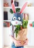 Gullig stilfull pojke, i polygonal easter kaninmaskering med en påse mycket av nya vårgräsplaner royaltyfri bild
