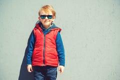 Gullig stilfull pojke som framme står av den gråa väggen utomhus Royaltyfria Foton
