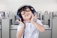 Gullig student Listening Music med hörlurar Arkivfoton