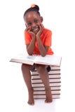Gullig svart afrikansk amerikanliten flicka som läser en bok - afrikan Fotografering för Bildbyråer