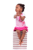 Gullig svart afrikansk amerikanliten flicka som placeras i en bunt av bu Arkivfoto