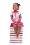 Gullig svart afrikansk amerikanliten flicka som placeras i en bunt av bu Arkivfoton