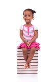 Gullig svart afrikansk amerikanliten flicka som placeras i en bunt av bu Arkivbilder