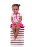 Gullig svart afrikansk amerikanliten flicka som placeras i en bunt av bu Royaltyfri Bild