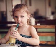 Gullig tänkande ungeflicka som dricker fruktsaft i kafé med allvarlig blick Arkivbilder