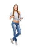 Gullig tillfällig tonårs- flicka med den digitala minnestavlan som gör en gest upp tummar Arkivfoto