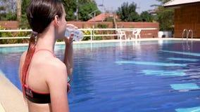 Gullig tonårig flicka i baddräktdricksvatten på poolsiden sund livsstil för begrepp video stock video