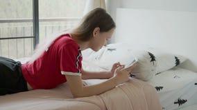Gullig tonårig flicka med rosa hårlekar på telefonen på säng arkivfilmer