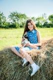 Gullig tonårig flicka med valpsammanträde på överkanten av höstacken Arkivbild
