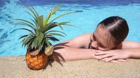 Gullig tonårig flicka som simmar till ananas i solglasögon på poolsiden för dublin för bilstadsbegrepp litet lopp översikt video stock video