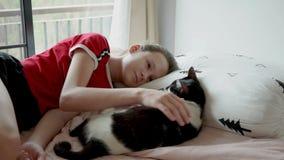 Gullig tonårig flicka som spelar med hennes katt på säng arkivfilmer