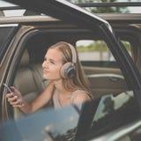 Gullig tonårs- flicka som lyssnar till hennes favorit- musik/audiobook på hig-slut hörlurar royaltyfri bild