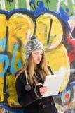 Gullig tonårs- flicka som utomhus använder minnestavladatoren Fotografering för Bildbyråer