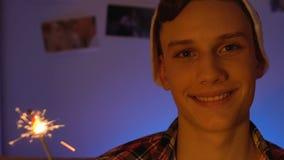 Gullig tonårs- pojke som rymmer bengal ljus som ler kameran, ungdompositivity, ferie stock video