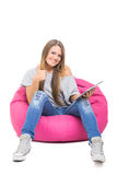 Gullig tonårs- flicka med minnestavlan som gör en gest upp tummar Royaltyfri Bild