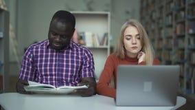 Gullig trött flicka med en bärbar dator och hennes afrikansk amerikanvän som läser en bok arkivfilmer