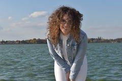 Gullig trendig flicka som ser kameran Lockig flicka nära sjön Royaltyfri Foto