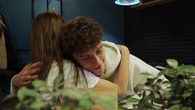 Gullig trevlig flicka att krama hennes unga pojkvän mycket försiktigt och sitta slappt vid tabellen i hemtrevligt kaffehus stock video