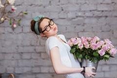 Gullig trött hållande tung hink för ung kvinna med rosa rosor Fotografering för Bildbyråer