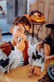 Gullig underhållen skolpojkekänsla, medan äta klibbiga sötsaker för allhelgonaafton royaltyfri foto