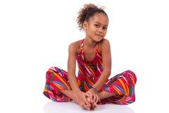 Gullig ung afrikansk asiatisk flicka i korrekt läge på golvet Arkivfoton