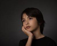 Gullig ung asiatisk pojke som ser upp med allvarlig blick på svart backg Fotografering för Bildbyråer
