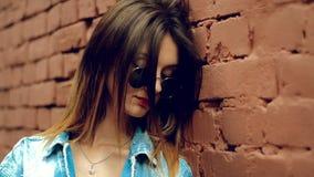 Gullig ung blondin i solglasögon med röda kantstans över en tegelstenvägg arkivfilmer